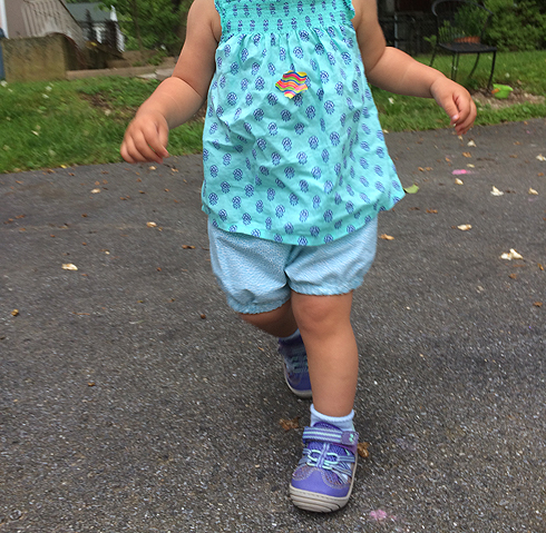 A toddler in shorts, with the head cropped out.