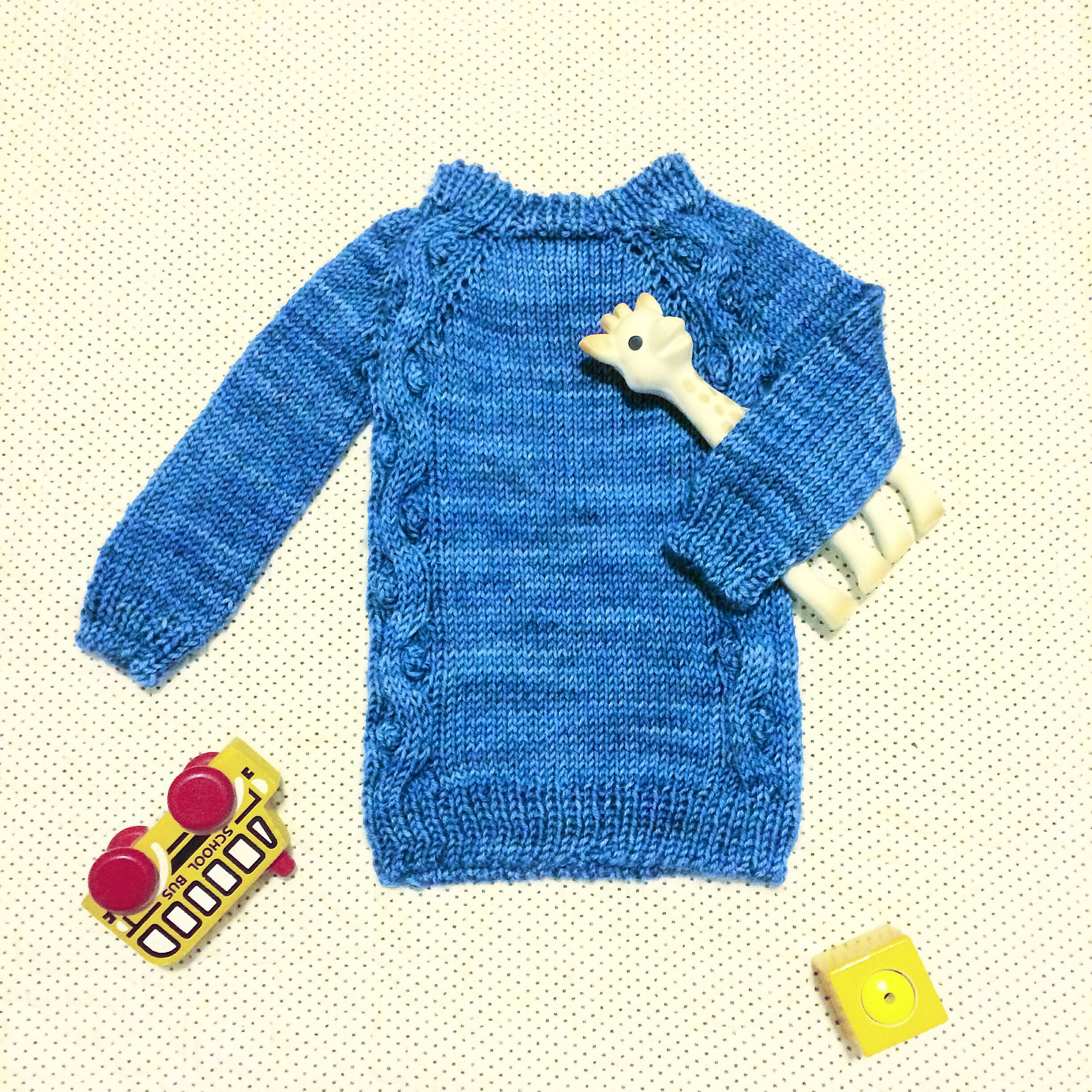 Blue baby sweater with toy giraffe, school bus, and block